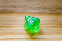 Un verde translúcido ocho echó a un lado jugando dados en un backgro de madera Imagenes de archivo