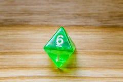 Un verde translúcido ocho echó a un lado jugando dados en un backgro de madera Fotografía de archivo