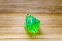 Un verde translúcido ocho echó a un lado jugando dados en un backgro de madera Imágenes de archivo libres de regalías