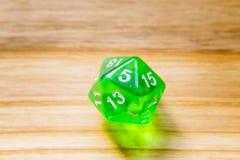 Un verde translúcido veinte echó a un lado jugando dados en un backgr de madera Foto de archivo