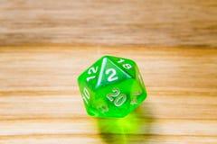 Un verde translúcido veinte echó a un lado jugando dados en un backgr de madera Imagen de archivo libre de regalías