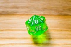 Un verde translúcido veinte echó a un lado jugando dados en un backgr de madera Fotografía de archivo libre de regalías