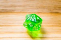 Un verde translúcido veinte echó a un lado jugando dados en un backgr de madera Imagenes de archivo