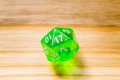 Un verde translúcido veinte echó a un lado jugando dados en un backgr de madera Imagen de archivo