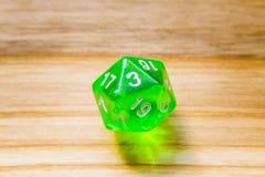 Un verde translúcido veinte echó a un lado jugando dados en un backgr de madera Fotografía de archivo