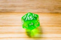 Un verde translúcido veinte echó a un lado jugando dados en un backgr de madera Fotos de archivo