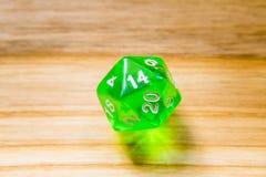 Un verde translúcido veinte echó a un lado jugando dados en un backgr de madera Imágenes de archivo libres de regalías