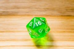 Un verde translúcido veinte echó a un lado jugando dados en un backgr de madera Fotos de archivo libres de regalías