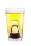 Un verre à liqueur a rempli de l'alcool, placé à l'intérieur d'un verre avec de la bière Photo libre de droits