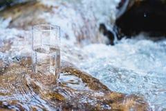 Un verre-verre avec de l'eau potable de montagne pure se tient sur une roche au cours d'une rivière de montagne contre le context photo libre de droits