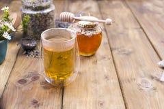 Un verre avec le thé, jaillissent les fleurs blanches Côté avec du miel Thé sec dans un pot Fond et espace libre en bois pour le  Photo libre de droits