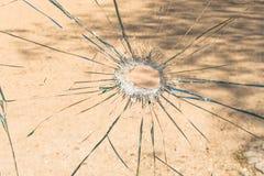 Un verre brisé avec un trou au milieu Images stock