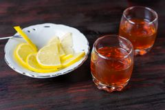 Un verre d'alcool et de citron coupé en tranches photos stock