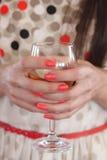Un verre dans les mains de la fille - faites la fête les personnes Image stock
