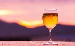 Un verre de bière avec le coucher du soleil Photographie stock
