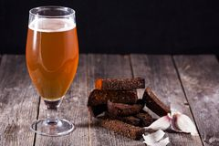 Un verre de bière blonde et de pains grillés aromatiques chauds frits d'ail de bl Images stock