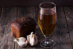 Un verre de bière blonde, un pain de pain noir et l'ail se trouvent sur t Photo stock
