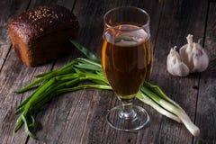 Un verre de bière blonde, un pain de pain noir, oignons verts frais Image libre de droits