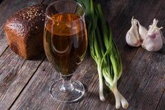 Un verre de bière blonde, un pain de pain noir, oignons verts frais Images libres de droits