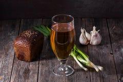 Un verre de bière blonde, un pain de pain noir, oignons verts frais Photo libre de droits