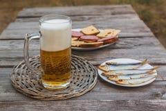 Un verre de bière blonde sur un fond des casse-croûte Foyer sélectif images stock