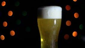 Un verre de bière froide sur un fond noir avec les lumières colorées est sur la barre La bière écume dans un verre HD banque de vidéos