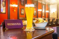 Un verre de bière non filtrée avec du fromage de biscottes, un comprimé - est réservé sur une table en bois dans la barre de rest photo libre de droits
