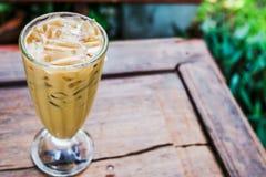 Un verre de café dans le jardin sur le plancher en bois Photographie stock