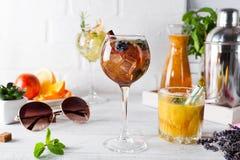 Un verre de cocktail avec de la cannelle, baies et sucre roux et un verre avec un cocktail orange ou frais et tonique Photo stock
