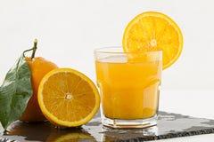 Un verre de invitation plein du jus d'orange avec la tranche orange sur la jante, une demi orange et entière avec la feuille sur  photos stock