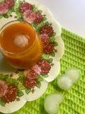 Un verre de jus de carotte frais avec de la glace se tient sur une serviette Tout près sur les glaçons de mensonge de table Photos libres de droits