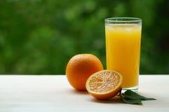 Un verre de jus d'orange avec de la glace et moitié d'orange Photos libres de droits