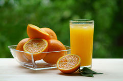 Un verre de jus d'orange avec une cuvette transparente pleine des oranges Photo stock