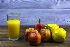 Un verre de jus d'orange fraîchement serré, de poires douces et de pommes image stock