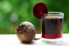 Un verre de jus de betteraves avec une tranche sur un verre Photographie stock