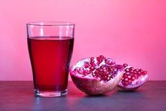 Un verre de jus de grenade avec la grenade porte des fruits sur la table en bois Concept sain de boissons Image libre de droits