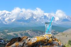 Un verre de l'eau clair comme de l'eau de roche sur le fond du mounta neigeux Images libres de droits