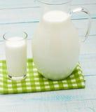 Un verre de lait et d'une cruche de lait sur la nappe de plaid Photographie stock