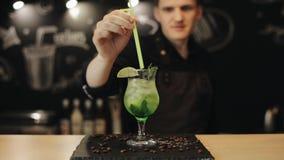 Un verre de mojito vierge d'isolement sur un compteur de barre Un barman met une paille verte dans la boisson banque de vidéos