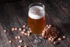Un verre de régénérer la bière blonde et une poignée dispersée de pist Photos stock