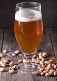 Un verre de régénérer la bière blonde et une poignée dispersée de pist Photo stock