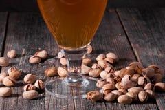 Un verre de régénérer la bière blonde et une poignée dispersée de pist Photo libre de droits