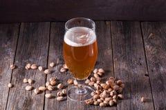 Un verre de régénérer la bière blonde et une poignée dispersée de pist Images stock