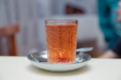 Un verre de thé noir Modelé et cuillère Thé dans une tasse en verre d'isolement sur un fond blured - image Clou et thé dans la ta images libres de droits