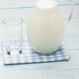 Un verre de vide et une cruche de lait sur la nappe de plaid Images libres de droits