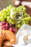 Un verre de vin avec des raisins, le fromage et le croissant rouges et verts photographie stock libre de droits