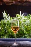 Un verre de vin blanc ou de jus de pomme se tient sur une table dans la bonne lumière avec un beau fond vert Image libre de droits