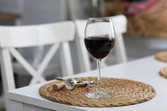 Un verre de vin et de quelques outils de vin sur une surface en bois blanche Vin rouge photo stock