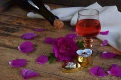 Un verre de vin rouge, de bouteille, de rose et anneau sur la table en bois rustique Anniversaire, jour du ` s de mère, jour du ` Image stock