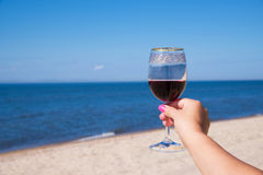 Un verre de vin rouge dans une belle main femelle avec les clous roses Contre le ciel ensoleillé bleu et la mer Image stock
